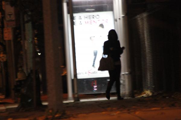 A young woman waits for a customer at a bus stop on lower Blue Hill Ave. in Boston. After the Combat Zone upgraded to luxury condos, four star restaurants, and new live theater venues- prostitution moved uptown, according to police