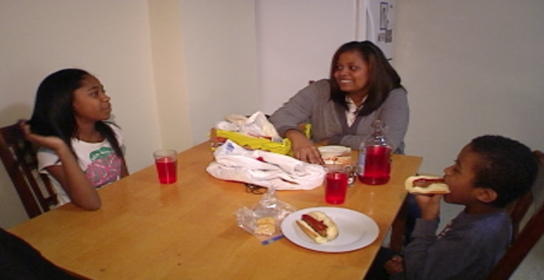 Dede Diggs sits down for dinner with her two children at her apartment in Dorchester.