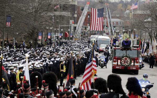 Firefighters salute as the funeral procession for Boston fire Lt. Edward Walsh arrives outside St. Patrick's Church in Watertown, Mass., Wednesday, April 2, 2014. Walsh and his colleague Michael Kennedy died after being trapped while battling a nine-alarm apartment fire in Boston on March 26.