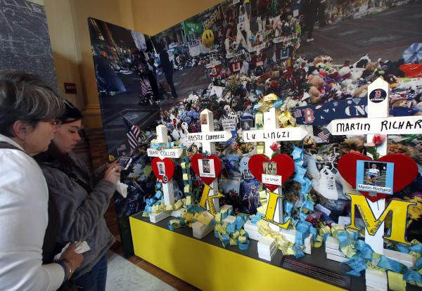 "Maryellen Lawler, far left, of Amesbury, Mass. stands with her daughter, Remy, as they look at crosses made for those killed at and in the aftermath of last year's Boston Marathon bombings, at an exhibit entitled ""Dear Boston: Messages from the Marathon Memorial"" at the Boston Public Library in Boston, Monday, April 7, 2014. Remy Lawler, a bombing survivor, said she was standing at the finish line area near Krystle Campbell, who perished."