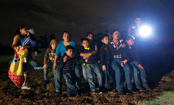 In this June 25, 2014 photo, a group of immigrants from Honduras and El Salvador who crossed the U.S.-Mexico border illegally are stopped in Granjeno, Texas. The epicenter of the recent surge in illegal immigration is a 5-mile slice of deep South Texas th