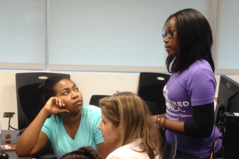 Tamina Johnson speaks with enrollment counselors Catherine Fuhrman and Xonjenese Jacobs
