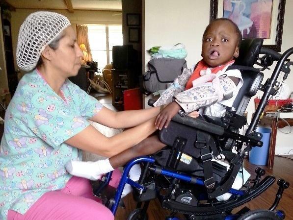 Registered Nurse Miriam Delgado cares for Matthew, a resident at an Orlando group home for medically  needy children.