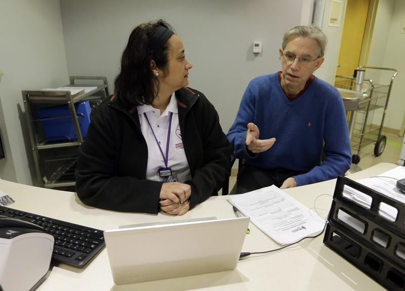 Chris Rogers, right, talks to Epilepsy Foundation Navigator Barbara Meneses as Rogers prepares to enroll for health care coverage, Tuesday, Jan. 12, 2015, in Coral Gables, Fla.