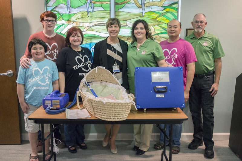 Crystal Hopkins' family gathers with LifePath Hospice employees during the presentation of the CuddleCot.