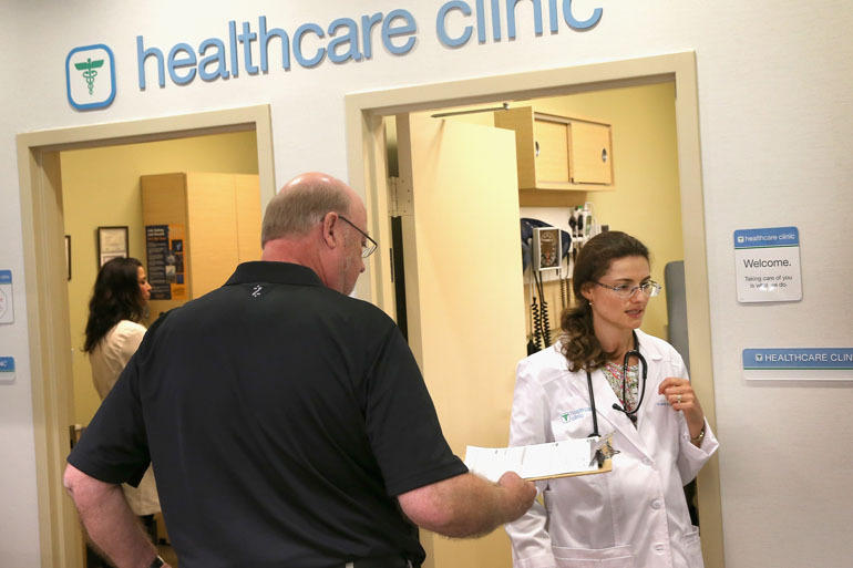 Ken Werner gives his health information to nurse practitioner Yana Dymarskiy before getting a flu vaccine at a Walgreens healthcare clinic in 2013 in Wheeling, Illinois.