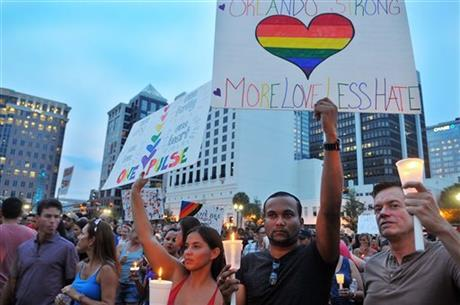 Stacy Timm, from left, Nizam Khan and Fabien Houle, all of Orlando, Fla., hold up signs and candles during a vigil at the Dr. P. Phillips Center for the Arts in Orlando on Monday, June 13, 2016.