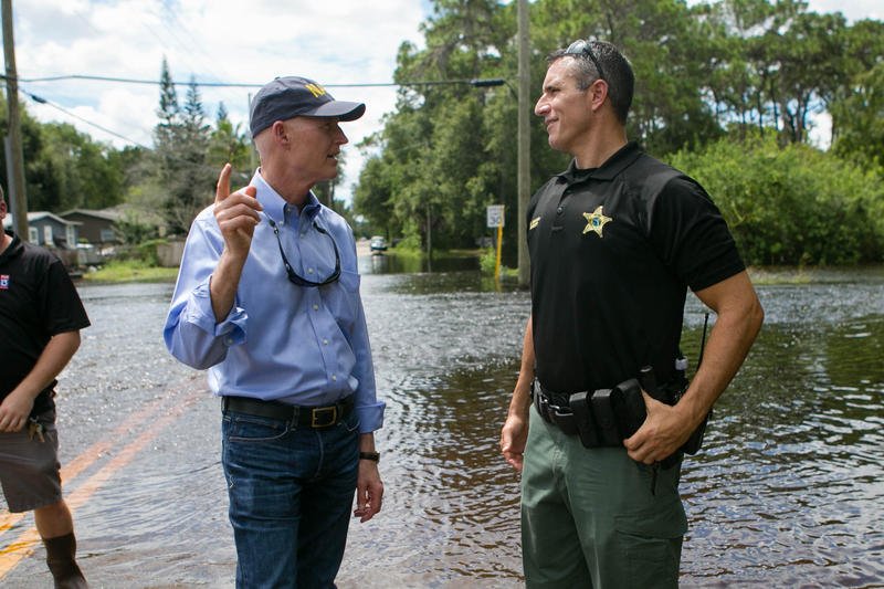Gov. Rick Scott talks with an emergency official during hurricane recovery.
