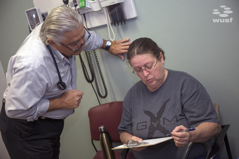 Dr. Ronald Cirillo, left, helps patient Deborah Hatfield fill out paperwork before getting a test to see whether she has hepatitis C.