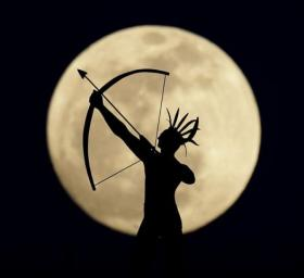 A full moon rises behind a statue of a Kansas Indian on top of the Kansas Statehouse in Topeka, Kansas