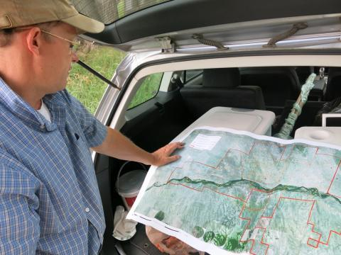 Burnidge checks a map of Fox Ranch that details the different areas Andrews can graze his cattle.
