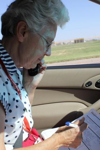 "Sister Janice Thome works in her ""office,"" a 2003 Ford Focus, as she helps a Garden City resident get help with a utility bill."