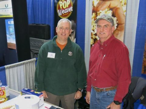 Dan Seaford (left), production manager at Weaver Popcorn, and grower Randy Fornall (right) work to convince field corn growers to put acres into popcorn at the 2013 farm show in Peoria, Ill.