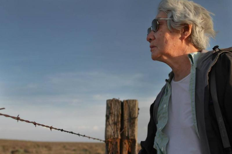 Lily Yuriko Nakai Havey looking past the barbed wire fence at Amache