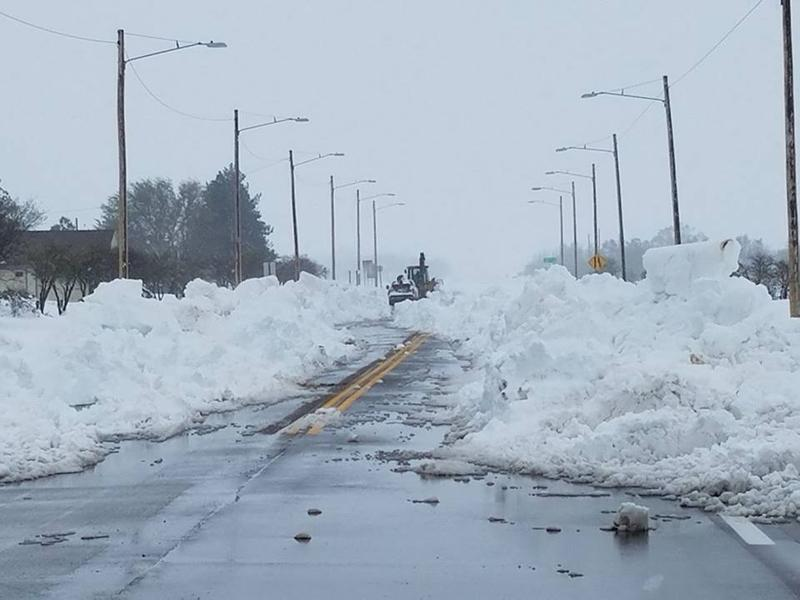 Crews worked to clear massive snow drifts on Highway 50, west of Lakin Sunday.