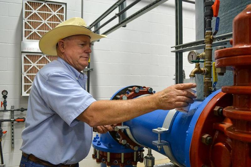 "Public Works Director Doug Hutcheson fills a cup with water at the water treatment plant in Wolfforth, Texas. ""We've tried to comply. We're team players. We're wanting to fix it and get it on down the road,"" he said."