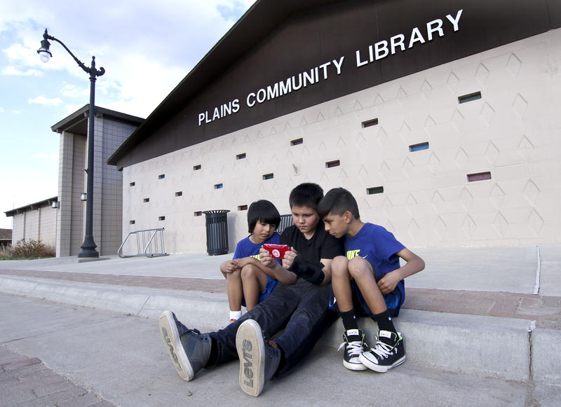 Angel Alvarez, center, holds his phone as he and Eduardo and Giovanni Alvarez watch Youtube videos. They're camped outside the library in Plains, Kansas, using the Wi-Fi signal because broadband can be hard to come by in town.