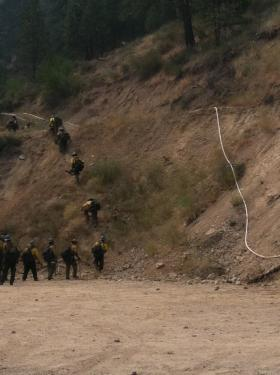 Fire fighters head up a hill to work on the Trinity Ridge Fire Thursday.