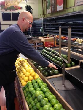 Dan Dolenar arranges produce at Whole Foods Market. The company's first retail store opens in Boise this morning.