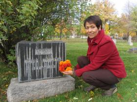 Ana Maria Schachtell at the gravestone of Jesus Urquides. The Idaho pioneer's gravesite will be covered with real and paper flowers as part of the Dia De Los Muertos celebration.