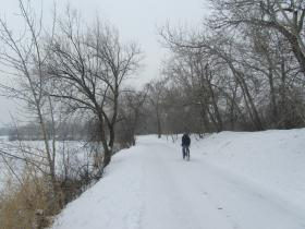 A bicyclist on the snowpacked Green Belt.