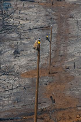 Idaho Power linemen work to restore power after wildfires moved through the area.
