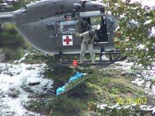 A member of the Idaho Air National Guard helps lift a plane crash victim away from a crash site in Owyhee County, ID on Sunday, May 27, 2012.  The three victims were flown to a Boise hospital.