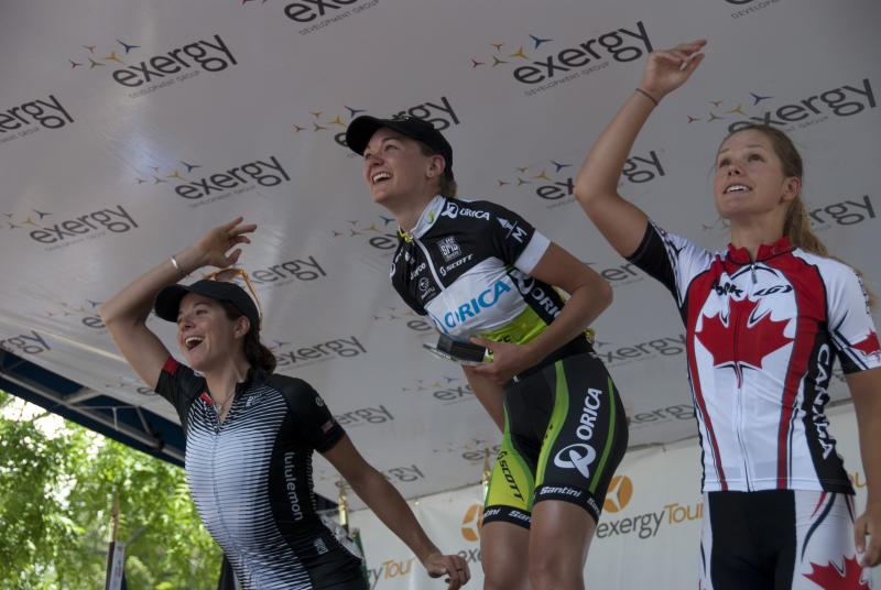 German rider Claudia Hausler of GreenEDGE – AIS won Monday's stage. She along with Evelyn Stevens (left) and third place finisher Jasmin Glaesser of the Canadian National Team toss their flowers into the cheering crowd.