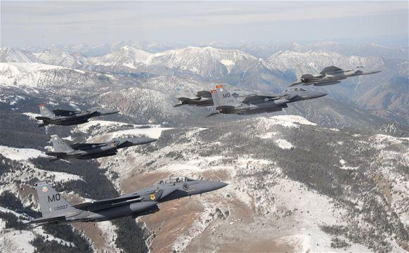 Six F-15C Eagle and F-15E Strike Eagles fly over the Sawtooth Mountains of Idaho.