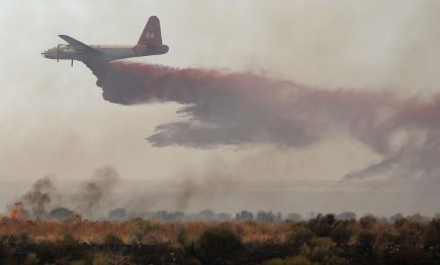 An aircraft drops fire retardant on the Kinyon Road Fire west of Castleford, Idaho on Sunday July 8, 2012.