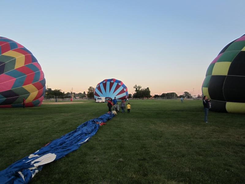The crew begins by pulling the hot air balloon out of it's sack.