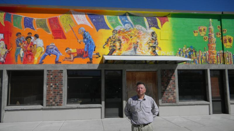 David Lin stands in front of the mural he commissioned for a building he owns in downtown Corvallis.