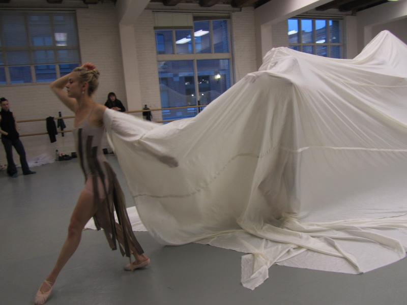 Dancers emerge one by one from under the cloth to begin a movement centered around the healing of all people.
