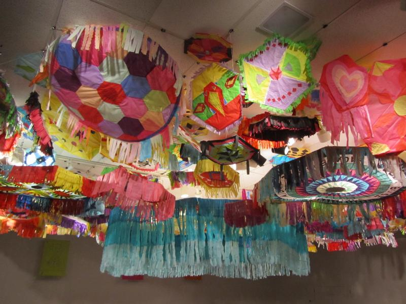 Giant paper tissue barriletas (kites) hang from a ceiling as part of the exhibit. Traditional barriletas adorn the graves and skies in Guatemala. The kites open the doorway to the dead and are burned at the end of the festivities.