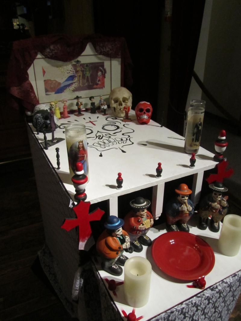 This is a traditional example of an altar that might be seen in Mexico or Central America. Artist Tony Rios decorated his piece with religious candles, calaveras (skeletons) and a plate for food to be shared with the dead.