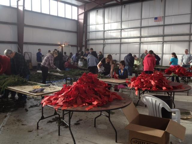 "Volunteers work in ""assembly line fashion"" to build 900 wreaths."