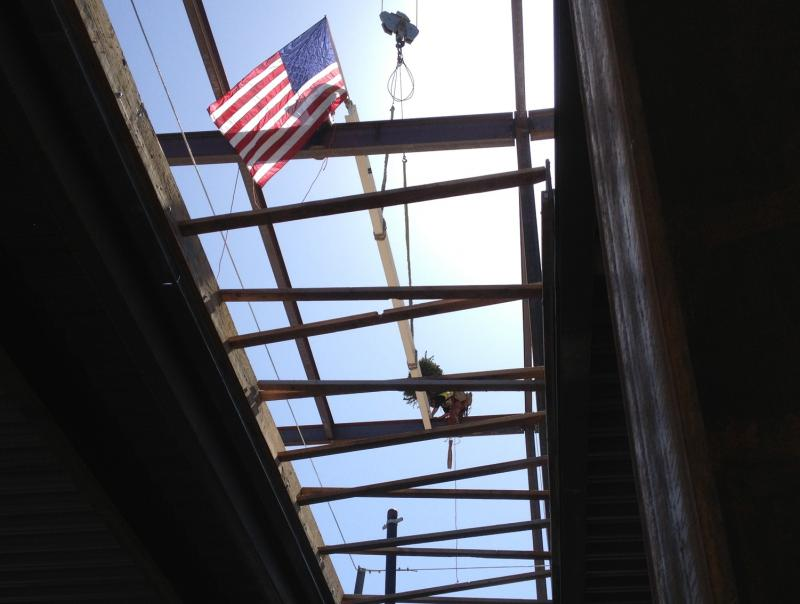 "The final beam is set atop the building. The ""topping off"" ceremony is a tradition among ironworkers."