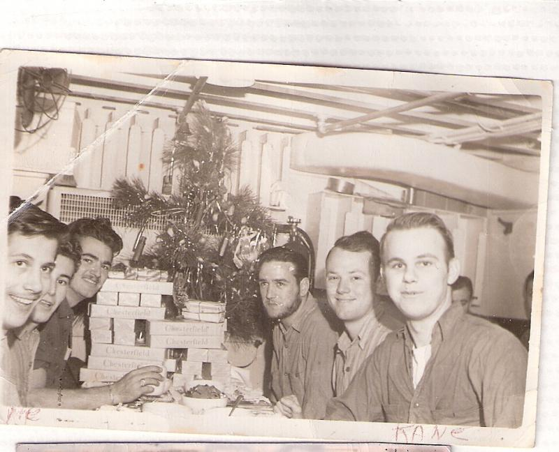 Christmas time on the USS Medrick.  Included in the photo are Eddie Fernandez, William Carhuff, and John Burns – sporting the beard.