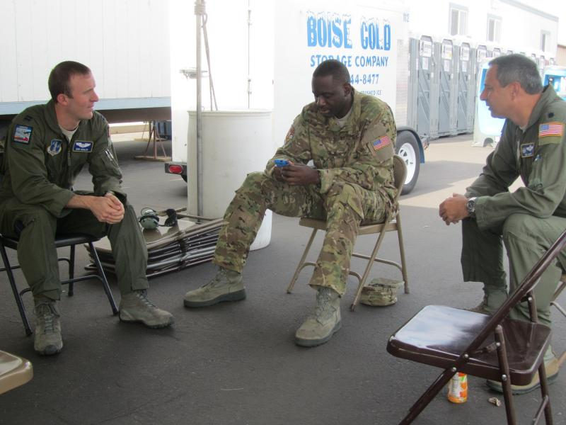 North Carolina Air National Guard members Robert Hegler of Lugoff, SC; Jermaine Parker of Charlotte, NC; and Tom Jacky of Matthews, NC sit under a tent at the Boise airport, waiting for orders from fire managers.