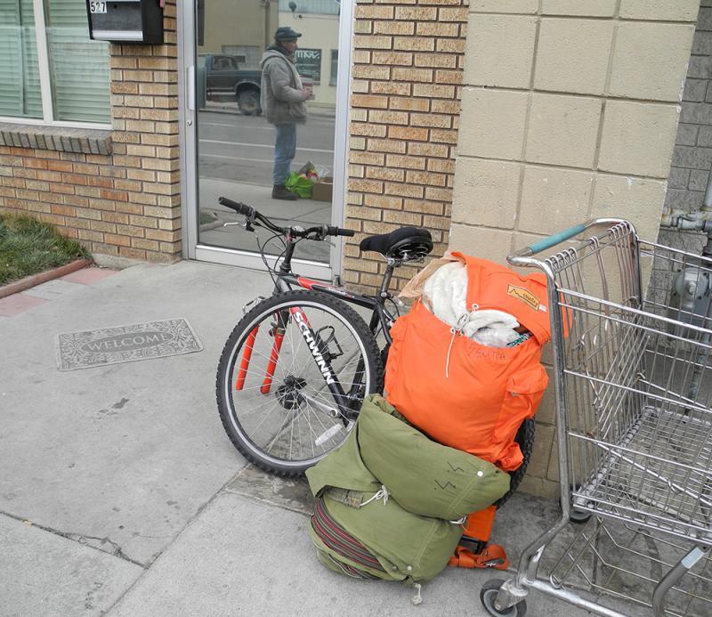 A bike, sleeping bag, and cart left ona sidewalk.