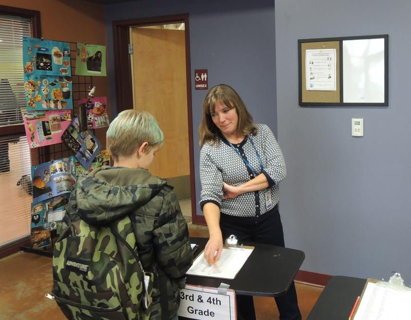 Barbara English makes sure kids sign in when they come to the Whitney Community Center after school.