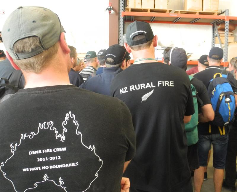 Aussie and Kiwi firefighters queue up for fire gear in a hanger at the National Interagency Fire Center in Boise.