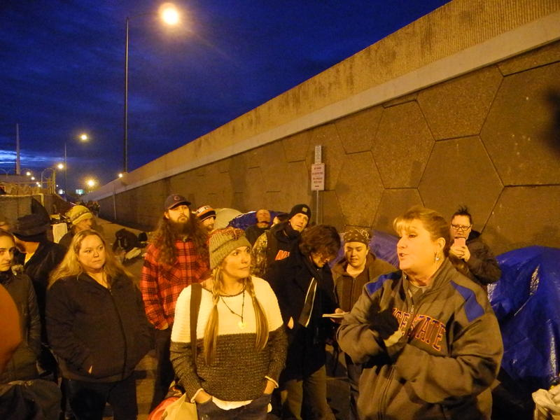 Homeless advocates Jodi Peterson (center) and Lisa Veaudry (right) explain to Cooper Court residents that police will clear the alley Friday.