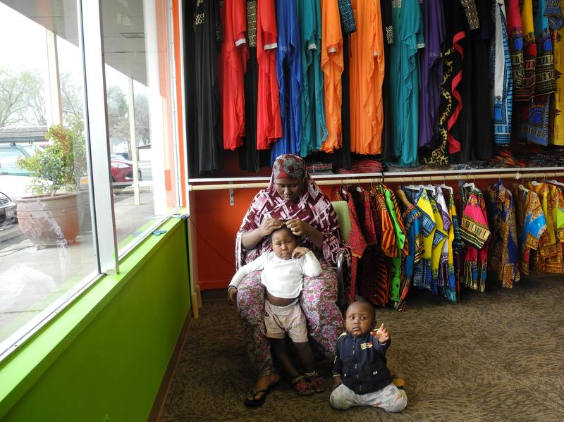 Mberwa does her daughter's hair while they wait for customers.