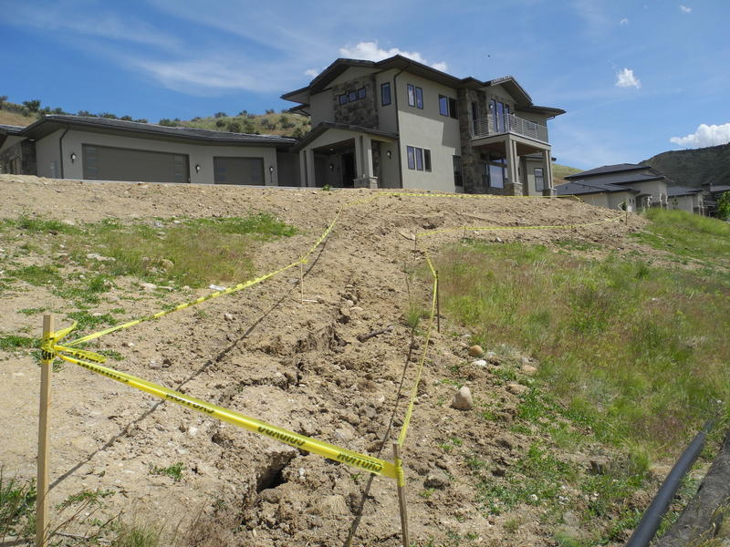 The shifting ground is outlined in the front yard of the house across the street from the unsafe property.