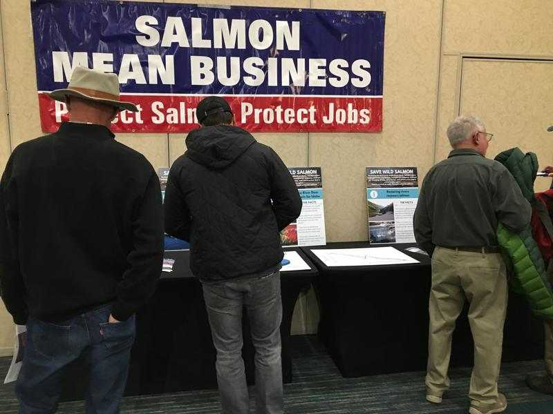 People read information in favor of removing four dams on the Snake River during a public meeting in Boise Tuesday. Conservationists say the dam removal is necessary, while opponents say fish are doing fine.