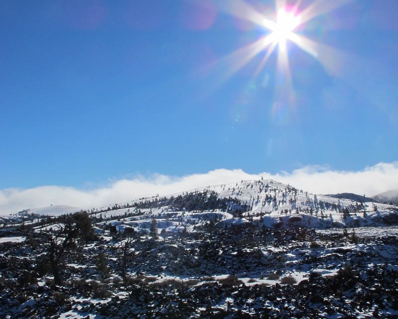 Bright sunshine spills across the, mist-shrouded rocky landscape of Craters of the Moon National Monument. Volcanic activity in the area took place as recently as 2,000 years ago.