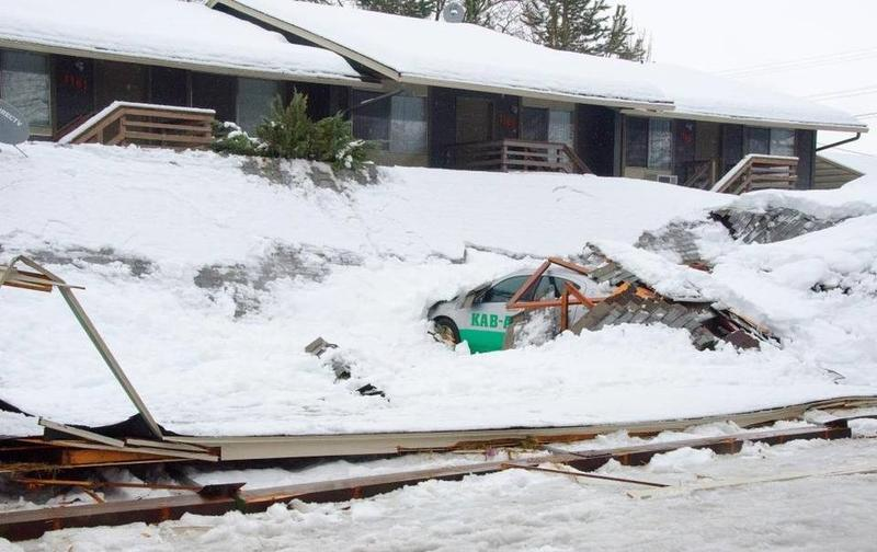 About a half-dozen cars are buried in debris Jan. 9 after a carport collapsed at a Boise apartment complex.