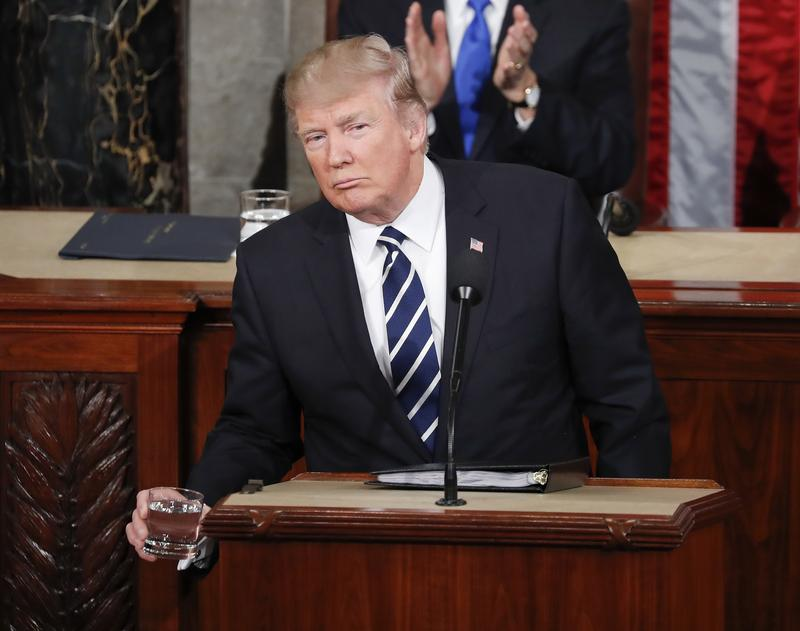 President Donald Trump reaches for a glass of water during his address to a joint session of Congress on Capitol Hill in Washington, Tuesday, Feb. 28, 2017.