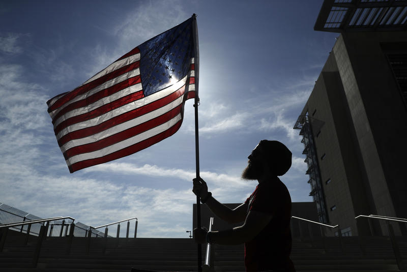 A protester holds up a flag outside of a federal courthouse, Monday, April 10, 2017, in Las Vegas.